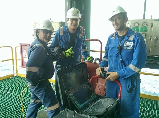 Three Proceanic employees from ROV team standing next to laptop