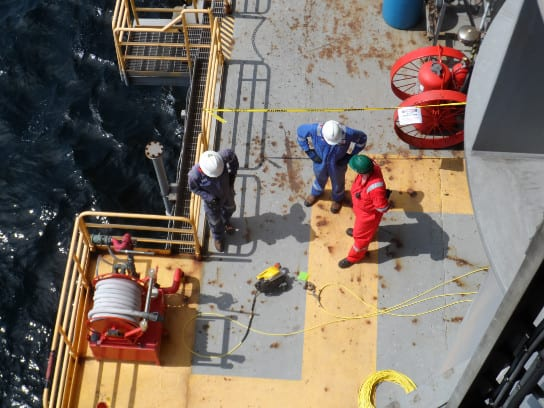 Three Proceanic employees on ship looking down at ROV